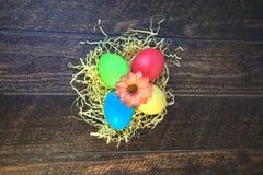 Τέσσερα χρωμάτισαν τα αυγά Πάσχας σε μια φωλιά του αχύρου με ένα λουλούδι στο κέντρο, βρίσκονται σε έναν ξύλινο πίνακα στοκ φωτογραφίες