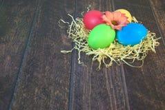 Τέσσερα χρωμάτισαν τα αυγά Πάσχας σε μια φωλιά του αχύρου με ένα λουλούδι στο κέντρο, βρίσκονται σε έναν ξύλινο πίνακα στοκ φωτογραφία με δικαίωμα ελεύθερης χρήσης