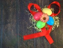 Τέσσερα χρωμάτισαν τα αυγά Πάσχας σε μια φωλιά του αχύρου με ένα λουλούδι στο κέντρο, που βρίσκεται σε μια ερυθρά κορδέλλα σε ένα στοκ φωτογραφίες
