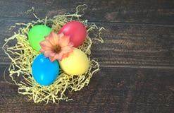 Τέσσερα χρωμάτισαν τα αυγά Πάσχας σε μια φωλιά του αχύρου με ένα λουλούδι στο κέντρο, βρίσκονται σε έναν ξύλινο πίνακα στοκ εικόνες