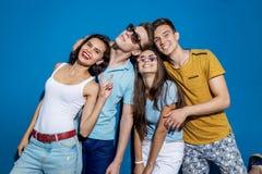 Τέσσερις όμορφοι φίλοι γελούν στεμένος μπροστά από τον μπλε τοίχο που ρίχνει τις βέβαιες και ευτυχείς ματιές στοκ φωτογραφία