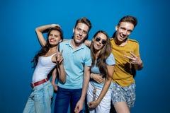 Τέσσερις όμορφοι φίλοι γελούν στεμένος μπροστά από τον μπλε τοίχο που ρίχνει τις βέβαιες και ευτυχείς ματιές στοκ φωτογραφία με δικαίωμα ελεύθερης χρήσης