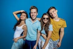Τέσσερις όμορφοι φίλοι γελούν στεμένος μπροστά από τον μπλε τοίχο που ρίχνει τις βέβαιες και ευτυχείς ματιές στοκ εικόνα με δικαίωμα ελεύθερης χρήσης