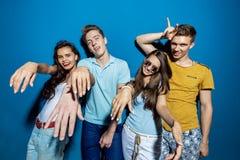 Τέσσερις όμορφοι φίλοι γελούν στεμένος μπροστά από τον μπλε τοίχο που ρίχνει τις βέβαιες και ευτυχείς ματιές στοκ φωτογραφίες