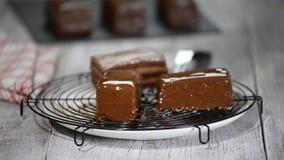 Τήξη σοκολάτας στο κέικ Έκχυση λούστρου σοκολάτας στο σπιτικό επιδόρπιο Κλείστε επάνω της διακόσμησης κέικ μπισκότων κάλυμμα φιλμ μικρού μήκους