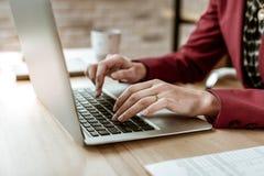Τακτοποιήστε την κατάλληλη επιχειρηματία στο κόκκινο ισχυρό σακάκι χρησιμοποιώντας το lap-top για την εργασία στοκ φωτογραφίες με δικαίωμα ελεύθερης χρήσης