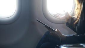 Ταμπλέτα γυναικείας εκμετάλλευσης στα χέρια, που μιλούν και που κάθονται στο αεροπλάνο απόθεμα βίντεο