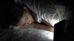 Ταμπλέτα παιχνιδιού παιδιών στη σκοτεινή νύχτα, κορίτσι που κοιτάζει βιαστικά Διαδίκτυο στο κρεβάτι, που δεν κοιμάται απόθεμα βίντεο