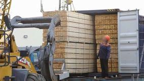 Τα άτομα φορτώνουν μια ξύλινη ακτίνα στο αυτοκίνητο, που φορτώνει το φορτίο στο αυτοκίνητο χρησιμοποιώντας έναν γερανό απόθεμα βίντεο