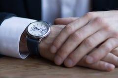 Τα άτομα παραδίδουν ένα κοστούμι με τις άσπρα μανσέτες και τα ρολόγια στο βραχίονα στοκ φωτογραφία με δικαίωμα ελεύθερης χρήσης