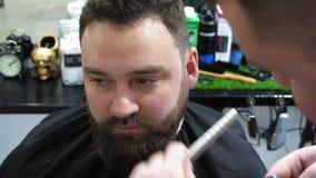 Τα αρσενικά χέρια του κομμωτή κόβουν τα φρύδια στο άτομο trimmer Τρίχα πελατών περικοπών κουρέων με μια επαγγελματική γενειάδα φιλμ μικρού μήκους
