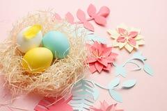 Τα αυγά Πάσχας Coloeful στη φωλιά στο υπόβαθρο χρώματος κρητιδογραφιών με το origami papercraft ανθίζουν τη διακόσμηση Διάστημα α στοκ εικόνες