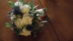 Τα γαμήλια δαχτυλίδια βρίσκονται κοντά στην όμορφη γαμήλια ανθοδέσμη στον ξύλινο πίνακα φιλμ μικρού μήκους
