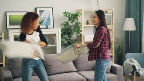 Τα ελκυστικά κορίτσια Ασιάτης και ο αφροαμερικάνος απολαμβάνουν την πάλη μαξιλαριών στο σπίτι που έχει τη διασκέδαση κατά τη διάρ φιλμ μικρού μήκους