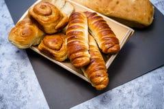 Τα εύγευστες ευώδεις σπιτικές κουλούρια και οι ζύμες των διαφορετικών μορφών με την κανέλα σχεδιάζονται στο ξύλινο πιάτο στοκ εικόνα με δικαίωμα ελεύθερης χρήσης