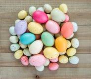 Τα ζωηρόχρωμα speckled αυγά Πάσχας συσσώρευσαν επάνω σε ένα ξύλινο υπόβαθρο στοκ φωτογραφία