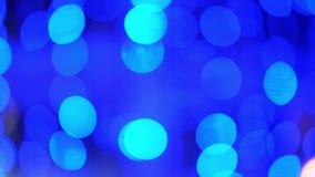 Τα θολωμένα bokeh ζωηρόχρωμα φανάρια φω'των, νέος φωτισμός έτους διακοπών στο μαύρο χειμώνα Χριστουγέννων υποβάθρου ακτινοβολούν  απόθεμα βίντεο
