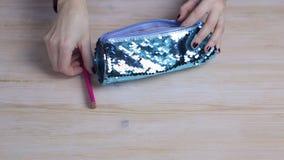 Τα κοριτσίστικα χέρια δίπλωσαν τα χρωματισμένα μολύβια σε μια περίπτωση μολυβιών απόθεμα βίντεο
