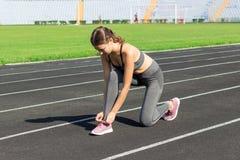 Τα νέα χέρια γυναικών δένουν τις δαντέλλες στα ρόδινα αθλητικά παπούτσια της σε ένα στάδιο, έτοιμο για το τρέξιμο, τον αθλητισμό  στοκ φωτογραφία