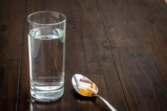 Τα διάφορα χάπια είναι σε ένα κουτάλι δίπλα σε ένα ποτήρι του νερού σε έναν καφετή πίνακα στοκ φωτογραφία με δικαίωμα ελεύθερης χρήσης