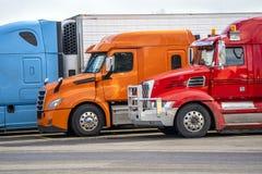 Τα φωτεινά μπλε πορτοκαλιά και κόκκινα μεγάλα ημι φορτηγά εγκαταστάσεων γεώτρησης που στέκονται στη σειρά στη στάση φορτηγών που  στοκ φωτογραφία με δικαίωμα ελεύθερης χρήσης