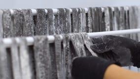 Τα χέρια βάζουν τα λωρίδες των μαύρων ζυμαρικών στα ράφια για την ξήρανση της κινηματογράφησης σε πρώτο πλάνο σε σε αργή κίνηση φιλμ μικρού μήκους