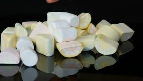 Τα χέρια ρίχνουν τις πολύχρωμες μίνι marshmallow καραμέλες στην επιφάνεια καθρεφτών και ένα μαύρο υπόβαθρο Το πρόβλημα του διαβήτ φιλμ μικρού μήκους