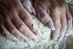 Τα χέρια της γυναίκας με η εργασία καρφιών με τη ζύμη στην κουζίνα στοκ φωτογραφίες