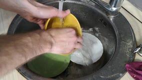 Τα χέρια των ατόμων του σπιτιού πλένουν τα πιάτα κάτω από την κινηματογράφηση σε πρώτο πλάνο τρεχούμενου νερού