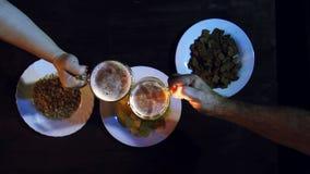 Τα χέρια των φίλων στο φραγμό στον πίνακα πρόχειρων φαγητών χτυπούν τις πλήρεις κούπες μπύρας από κοινού απόθεμα βίντεο