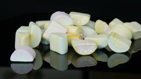 Τα χέρια παίρνουν τις πολύχρωμες μίνι marshmallow καραμέλες στην επιφάνεια καθρεφτών και ένα μαύρο υπόβαθρο Το πρόβλημα του διαβή φιλμ μικρού μήκους