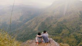 Τα πίσω ευρέα πυροβοληθε'ντα ευτυχή newlyweds άποψης κάθονται μαζί να αγκαλιάσουν κάτω από τη βροχή στο ταξίδι μήνα του μέλιτος σ φιλμ μικρού μήκους