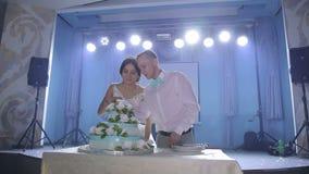 Τα newlyweds κόβουν ένα όμορφο άσπρο γαμήλιο κέικ με τα λουλούδια απόθεμα βίντεο