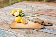 Τεμαχισμός του τέμνοντος πίνακα με το τεμαχισμένα λεμόνι, το βάζο, τα φύλλα μεντών, το μαχαίρι και το άχυρο στον ξύλινο πίνακα Πρ στοκ εικόνα