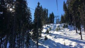 Τεσσάρων ατόμων ανελκυστήρας καρεκλών σκι που περνά από τα δέντρα επάνω ένα βουνό με έναν μπλε ουρανό απόθεμα βίντεο