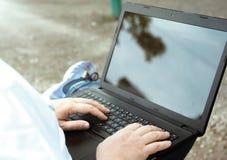 Τεχνολογία και επικοινωνία, εργασία στο πληκτρολόγιο με ένα lap-top υπαίθρια, στοκ φωτογραφία