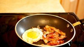 Τηγάνισμα μπέϊκον και αυγών στο καυτό τηγάνι τηγανητών στο στενό επάνω συνδετήρα με την εκλεκτική εστίαση απόθεμα βίντεο