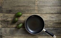 Τηγάνι με το αβοκάντο φρούτων στον πίνακα κουζινών στοκ εικόνα με δικαίωμα ελεύθερης χρήσης