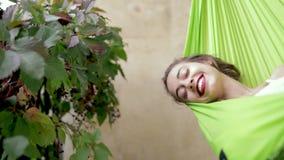 Την ευτυχή νέα γυναίκα που χαλαρώνουν βρίσκεται σε μια αιώρα στο σπίτι μπαλκονιών Η γυναίκα basks και κάνει ηλιοθεραπεία σε μια α φιλμ μικρού μήκους