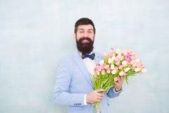 Τουλίπες για τον αγαπημένο Το άτομο εκαλλώπισε καλά την ανθοδέσμη λουλουδιών λαβής δεσμών τόξων σμόκιν ένδυσης Την προσκαλέστε πο στοκ φωτογραφίες