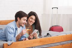 Τουρίστες που κρατούν τα εισιτήρια, που χρησιμοποιούν το τηλέφωνο και την πιστωτική κάρτα στοκ εικόνα
