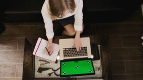 Τοπ άποψη ενός ξανθού κοριτσιού με ένα lap-top που λειτουργεί και παίρνει τις σημειώσεις σε ένα σημειωματάριο εσωτερικό δάσος πρά απόθεμα βίντεο