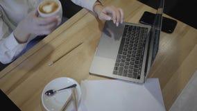 Τοπ άποψη της γυναίκας που χρησιμοποιεί το lap-top της σε έναν καφέ ή ένα εστιατόριο Υπερυψωμένος πυροβολισμός της νέας συνεδρίασ απόθεμα βίντεο