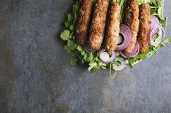 Τοπ άποψη του τύπου kebab-lule kebab με τα χορτάρια και το τεμαχισμένο κρεμμύδι στο σκοτεινό πίνακα Διάστημα αντιγράφων για το κε στοκ φωτογραφίες