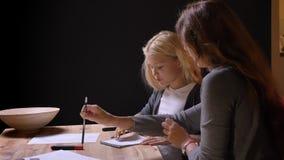 Τοπ βλαστός κινηματογραφήσεων σε πρώτο πλάνο της νέας καυκάσιας μητέρας που βοηθά το μικρό κορίτσι της με την εργασία στο άνετο σ απόθεμα βίντεο