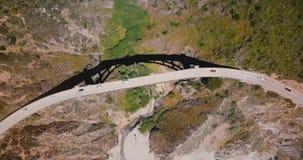 Τοπ κηφήνας άποψης που αυξάνεται και που περιστρέφει επάνω από τη γέφυρα κολπίσκου Bixby σε μεγάλο Sur με την κυκλοφορία, που απο απόθεμα βίντεο
