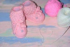 Το άσπρος-ροζ έπλεξε τις λείες παπουτσιών μωρών σε έναν ρόδινος-μπλε ξύλινο πίνακα με τις σφαίρες του νήματος και μιας καρδιάς τω στοκ εικόνα