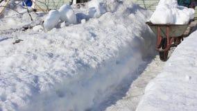 Το άτομο ελευθερώνει το χιόνι από στο εξοχικό σπίτι στο τέλος του χειμώνα απόθεμα βίντεο