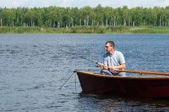 Το άτομο κάθεται σε μια βάρκα και πιάνει τα ψάρια με την περιστροφή στον ποταμό στοκ φωτογραφία