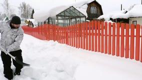 Το άτομο καθαρίζει το πεζοδρόμιο από το χιόνι απόθεμα βίντεο